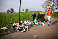 © Licensed to London News Pictures. 31/03/2021. London, UK. A local resident clears up some of the huge amounts of rubbish left scattered around Primrose Hill in North West London this morning after sunbathers and picnickers enjoy the hottest day of the year yesterday as weather forecasters predict further highs of 23c in the South East today. Photo credit: Alex Lentati/LNP