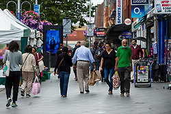 © Licensed to London News Pictures. 20/08/2021. LONDON, UK.  People shopping in the town centre of Harrow-on-the-Hill, north-west London.  The Office for National Statistics (ONS) has announced that UK retail sales dropped in July to their lowest level since shops reopened in April with retailers reporting that Euro 2020 football tournament and bad weather kept shoppers away from stores.  Photo credit: Stephen Chung/LNP