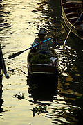 17 JANUARY 2013 - DAMNOEN SADUAK, RATCHABURI, THAILAND: A woman paddles her canoe through the Damnoen Saduak (also spelled Damnoensaduak) floating market. The floating market in Damnoen Saduak is one of the best known tourist attractions in Thailand. The canal was dug in the 1860's to connect to provincial towns south of Bangkok. At the time it was the straightest, longest canal in Thailand. Thousands of tourists, both foreign and Thai, visit Damnoen Saduak to see the floating market and experience canal life.     PHOTO BY JACK KURTZ