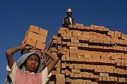 Child carrying bricks. In areas of Madagascar where the soil is lateritic houses are built from home-made bricks. It is a labour intensive process from digging up surrounding soil, individually moulding them, building kilns and using large quantities of fire wood. Dried bricks are then carried on the heads of usually the women and children to where they are to be used or sold.<br /> MADAGASCAR