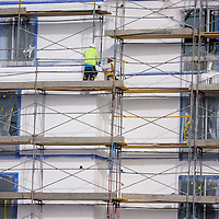 Construction workers do paint and stucco work while on a scaffolding on the site of a new Marriott hotel in Gallup Thursday.