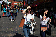 Young Chinese women shielding their eyes from the sun on Gerrard Street, Soho, also known as Chinatown in London, United Kingdom. The present Chinatown is in the Soho area occupying the area in and around Gerrard Street. It contains a number of Chinese restaurants, bakeries, supermarkets, souvenir shops, and other Chinese-run businesses and is in itself a major tourist destination.