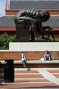 Two women relax in the sun in the courtyard of the British Library. They sit beneath a giant bronze statue of Isaac Newton ('Newton' after William Blake) by Eduardo Paolozzi. London, UK