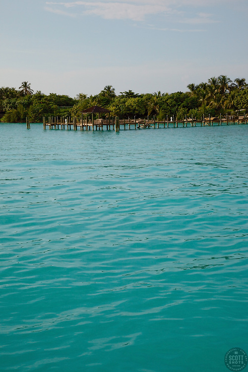Aqua water in the Bahamas with a dock in the background.