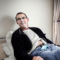 Nederland, Alkmaar , 7 oktober 2009. .Het Medisch Centrum Alkmaar (MCA) neemt vanaf september als eerste ziekenhuis in Noord-Holland 24 uur per dag patiënten op die een TIA hebben gehad..Bij een TIA (Transient Ischaemic Attack) krijgt een deel van de hersenen tijdelijk te weinig bloed, waardoor sommige hersencellen een moment minder goed of helemaal niet werken..Volgens MCA-neuroloog Majid Aramideh is het heel belangrijk dat patiënten direct de huisarts bellen wanneer zich uitvalsverschijnselen voordoen...Op de foto TIA patient met meetapparatuur op zijn buik die 24 uur eventuele hartritme stoornissen in de gaten houdt..24 hours a day the Medical Center Alkmaar (MCA) is the first hospital is taking in  patients who have had a TIA.