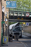 An MoT testing centre and the damaged aftermath of a lorry at Loughborough Junction after it crashed into one of the railway bridges - a main transport route for commuters into the City, on 8th May 2018, in south London, England. One person was injured.