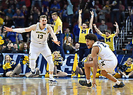 Michigan Wolverines guard Jordan Poole (2) celebrates with his teammate Moritz Wagner (13) after making the game-winning three-point shot to defeat the Houston Cougars in the second round of the 2018 NCAA Tournament at INTRUST Bank Arena.