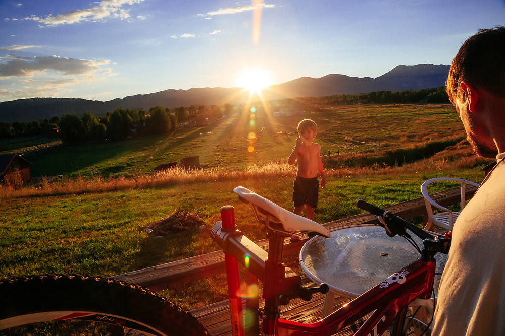 Jay and Micah Goodrich work on a mountain bike outside on the back deck as the sun decends to the horizon behind the Tetons in Wyoming.