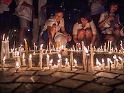 19 JANUARY 2014 - BANGKOK, THAILAND: Thais light a circle of candles on the ground in Banjasiri Park in Bangkok. Hundreds of people came to Benjasiri Park, a few hundred meters from the anti-government protest site in Asok Intersection, Sunday evening to pray for peace and rally for a respect for democracy Sunday. The vigil took place a few hours after a two explosive devices, thought to be grenades, were thrown at the protest site near Victory Monument, several kilometers north of Asok. The grenade attack Sunday was the 2nd daytime grenade attack in three days on anti-government protestors. No arrests have been made in the incidents.    PHOTO BY JACK KURTZ