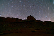 Time lapse Image of star trails and a butte in a remote section of the Island in the Sky District of Canyonlands National Park, San Juan County, Utah, USA.