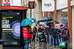 © Licensed to London News Pictures. 23/12/2020. London, UK. Last minute Christmas shoppers queue in the pouring rain outside M&S in Chelsea, South West London as fears grow that the whole of the UK will be plunged into Tier 4 restrictions after a Covid-19 mutation spread rapidly throughout the South East of England. Ministers have said that Downing Street is considering whether to add more areas of England to tougher Covid-19 restrictions after the new mutated strain continues to spread. Photo credit: Alex Lentati/LNP