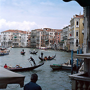 The Uniquely Romantic City of Venice was built entirely on water. The City stretches across 118 small islands in the marshy Venetian Lagoon along the Adriatic Sea in Northeast Italy. Narrow alleyways and canals pass between palaces and magnificent churches while Venice's unique Gondolas have been the source of transport along the city's canals since the eleventh century.  A man watches the Gondolas on the Grand Canal on May 03, 2008 in Venice, Italy. Photo Tim Clayton