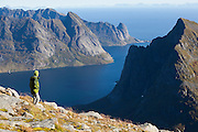 Liana Welty looks out towards Reine and Reinefjorden from below the summit of Hermannsdalstinden, the highest mountain in western Lofoten Islands, Norway.