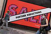 Shoppers wearing face masks walk past Selfridges whose Summer Sale is advertised in their window banners on Oxford Street in the West End on Covid 'Freedom Day'. This date is what Prime Minister Boris Johnson's UK government has set as the end of strict Covid pandemic social distancing conditions with the end of mandatory face coverings in shops and public transport, on 19th July 2021, in London, England.