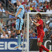 Edin Dzeko, (left), Manchester City, wins a header while challenged by Sebastian Coates, Liverpool, during the Manchester City Vs Liverpool FC Guinness International Champions Cup match at Yankee Stadium, The Bronx, New York, USA. 30th July 2014. Photo Tim Clayton