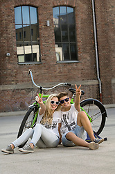 Teenage couple sitting on street with bicycle and showing peace sign, smiling