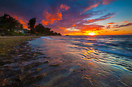 The sun and clouds provide a dramatic look to the end of the day along the North Shore of Oahu, Hawaii.