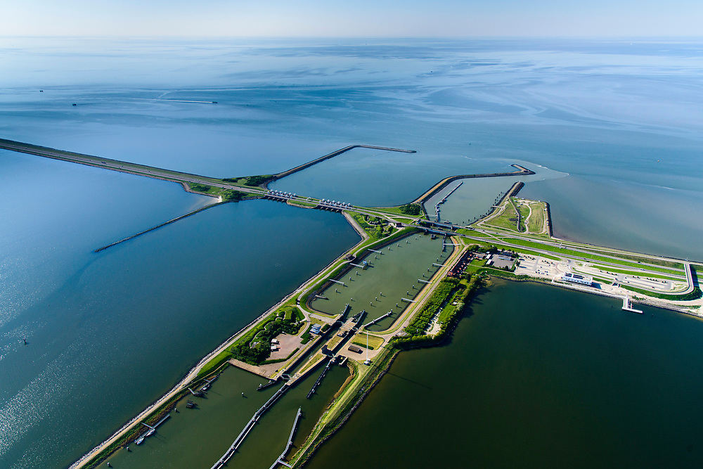 Nederland, Friesland, Gemeente Wonseradeel, 07-05-2018; Afsluitdijk ter hoogte van Kornwerderzand. Op het voormalig werkeiland liggen de Lorentzsluizen, een complex van spuisluizen en schutsluizen. De spuisluizen (uitwaterende sluizen) lozen van het IJsselmeer op de Waddenzee (boven). De sluizen worden beschermd door kazematten (bunkers). <br /> Enclosure Dam at the height of Kornwerderzand. On the former work island the Lorentz locks, a complex of sluices and locks. The sluices sluice surplus water to the Wadden sea (top). The locks are protected by bunkers.<br /> luchtfoto (toeslag op standard tarieven);<br /> aerial photo (additional fee required);<br /> copyright foto/photo Siebe Swart