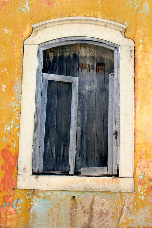 Abandoned window set against aged yellow plaster wall, Algarve Portugal