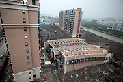 "A view of a collapsed apartment building at the ""Riverside Lotus"" developement in Shanghai, China on 29 June 2009.  Frenzied construction pace throughout China's ongoing building boom, the largest in recorded history, has left much to be wondered about safety and quality, as the toppling of this nearly finished 11 story apartment complex demonstrates."