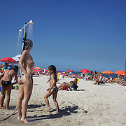 A beach scene as beach goers use showers on Ipanema beach, Rio de Janeiro,  Brazil. 31st July 2010. Photo Tim Clayton.
