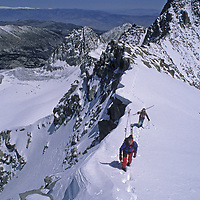 Skiers ascend the summit of Polemonium Peak in the Palisade Glacier region of California's Sierra Nevada.  Their objective is to ski the steep V-Notch Couloir below and left of them.  Mount Sill rises behind them and the Palisade Glacier lies below.