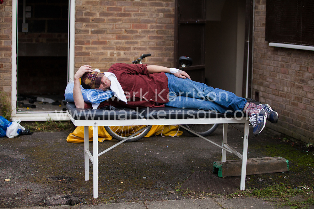 A housing activist rests on a makeshift bed close to the home of Mostafa Aliverdipour, the last remaining resident of the Sweets Way housing estate, on 23rd September 2015 in London, United Kingdom. A group of housing activists calling for better social housing provision in London had occupied some of the properties on the 142-home estate in Whetstone, in some cases refurbishing properties intentionally destroyed by the legal owners following eviction of the original residents, in order to try to prevent or delay the eviction of Mr Aliverdipour and the planned demolition and redevelopment of the entire estate by Barnet Council and Annington Property Ltd.