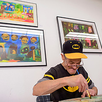 """091114       Cable Hoover<br /> <br /> Artist Jay Dickens works on a new piece as he sits among work already hung the Outsider Gallery group show """"Nervosis Explosis"""" Friday at Art123 Gallery in Gallup."""