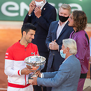 PARIS, FRANCE June 13.   Former Roland Garros champion Bjorn Borg present the winners trophy to Novak Djokovic of Serbia watched Jim Courier, a distraught Stefanos Tsitsipas of Greece and FFT President Gilles Moretton after the Men's Singles Final at the 2021 French Open Tennis Tournament at Roland Garros on June 13th 2021 in Paris, France. (Photo by Tim Clayton/Corbis via Getty Images)