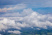 Airplane aerial view of clouds, blue sky, agricultural land below over Thailand