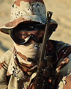 1991, North Carolina, USA --- A United States Army Special Forces sniper wears a face scarf and desert camouflage and carries a squad automatic weapon (SAW). --- Image by © Leif Skoogfors/CORBIS