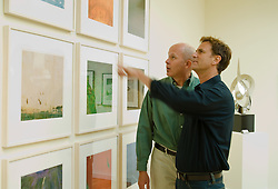 Gay couple looking at a wall of framed artwork in an art gallery