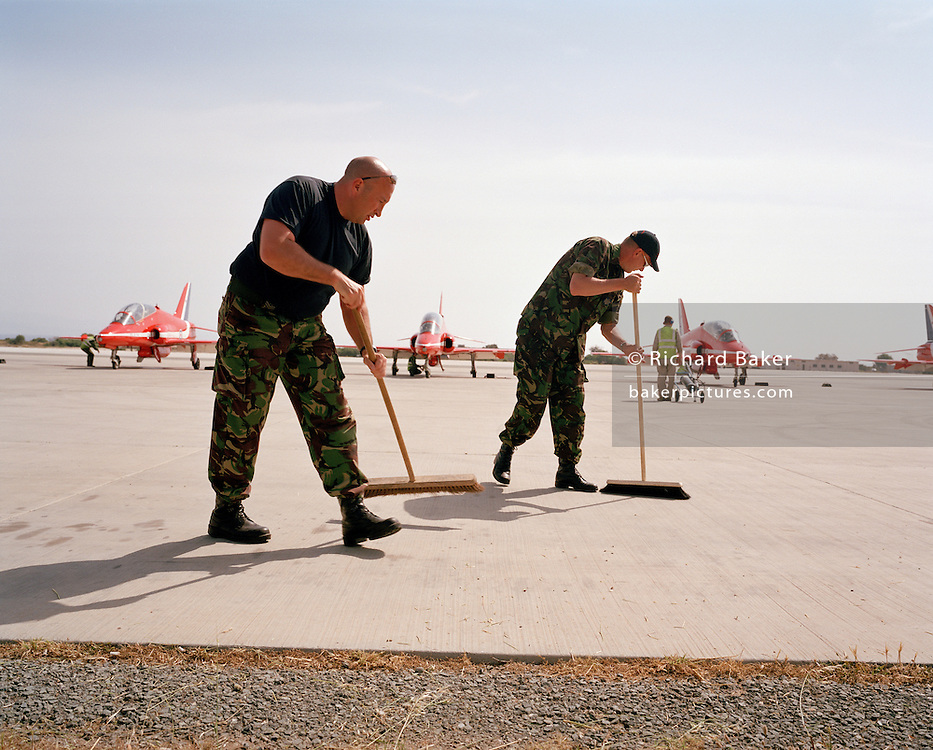Ground crew of the 'Red Arrows', Britain's Royal Air Force aerobatic team sweep foreign objects from airfield apron.