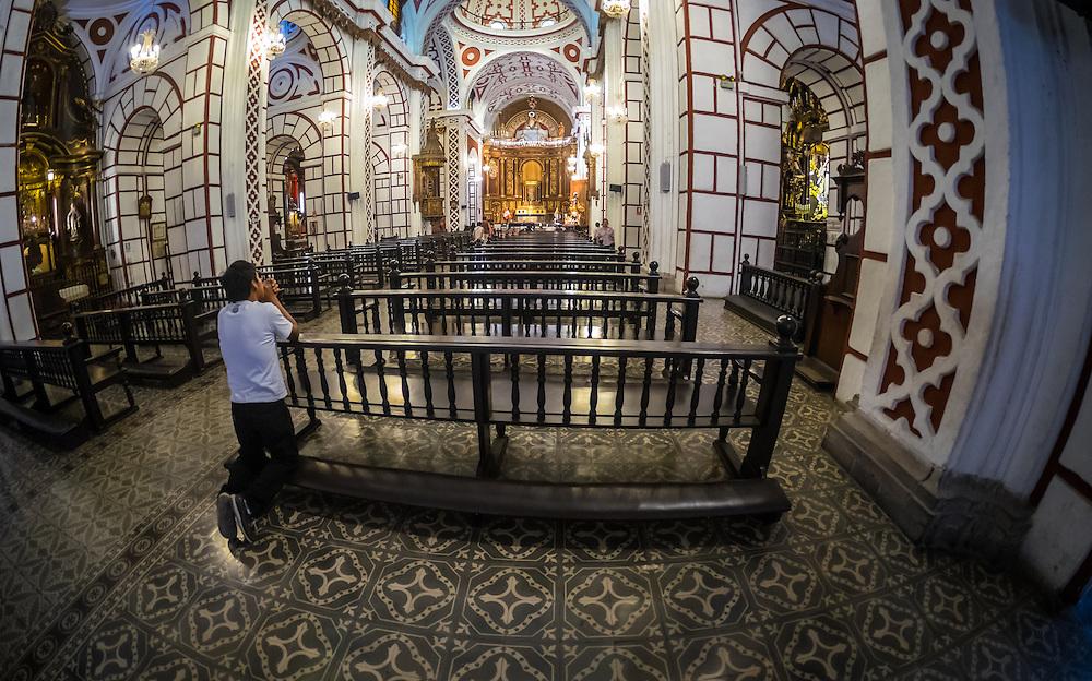 LIMA, PERU - CIRCA APRIL 2014: Man worshiping at the Monastery of San Francisco in the Lima Historic Centre in Peru