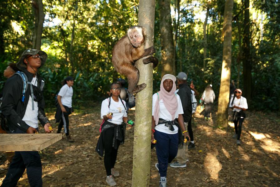 Frank Ski Kids feed monkeys while hiking on Isla Monos (Monkey Island).