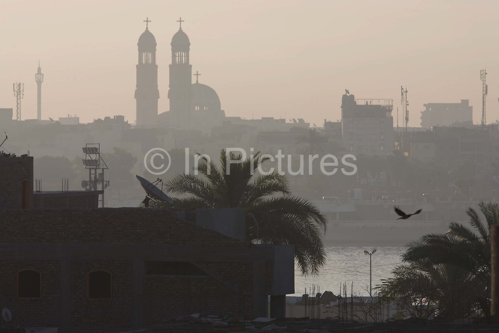 Looking East from the West Bank, early light over the River Nile and city of Luxor with its twin spires of the Christian Manak church, Nile Valley, Egypt. A bird flies past the open river and a satellite TV dish points to the sky. Luxor is a city in Upper (southern) Egypt and the capital of Luxor Governorate. About 95% of the country's 82.5 million (2012 est.) people live along the banks of the Nile throughout the Nile Delta, which fans out north of Cairo; and along the Suez Canal. These regions are among the world's most densely populated.