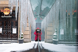 "© Licensed to London News Pictures. 28/02/2018. <br /> <br /> A woman stops to photograph icicles that have formed outside Buchanan Street Subway Station as Glasgow, Scotland is hit with snow storm ""Beast from the East"" on 28th February 2018.<br /> <br /> Photo credit should read Max Bryan/LNP"
