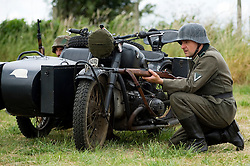 A re-enactor from the Northern World War Two Association Living History group, portraying a Gefreiter of the Panzer-Grenadier-Division Grossdeutschland, takes a firing position with his Mauser K98 rifle behind a BMW R71 motorcycle and sidecar during a large scale battle re-enactment..<br /> SPAM 1940's Weekend. Heckmonwyke near Wakefield 10 July 2010 <br /> Images © Paul David Drabble