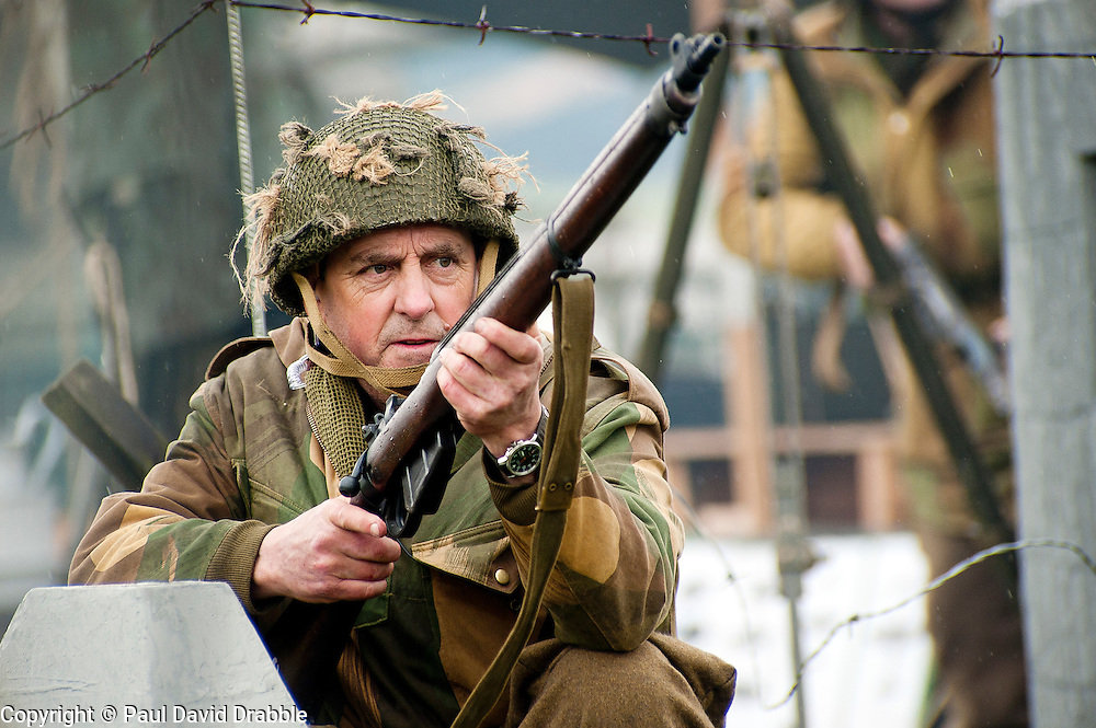 Renecator portraying a British Paratrooper from the 6th Airborne Division takes aim with his Lee Enfield rifle during a battle reenactment at Fort Paull Monday<br /> 7 May 2012<br /> Image © Paul David Drabble