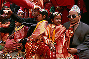 Fathers hold their daughters in their laps as they give them away in marriage at the girls' Ihi ceremony, a mock marriage to the Hindu god Vishnu, in Patan in the Kathmandu Valley, Nepal. Among the Newars, who are the original inhabitants of the Kathmandu Valley, every girl goes through this ceremony sometime between the age of five and ten. The Ihi makes the girl a full member of her father's family and caste and is also said to make sure that she will never become a widow, even if later on her future human husband would die, since she will forever be married to the god Vishnu. The Ihi is therefore for the Newar women a protection against the stigmatization of widows otherwise common in Hindu culture.