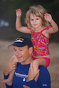 A father with his small daughter on his shoulders on the beach in Hawaii