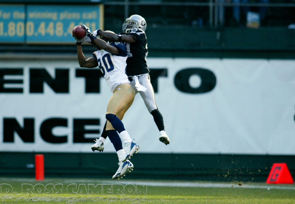 St. Louis Rams wide receiver Isaac Bruce (80) outleaps Oakland Raiders cornerback Fabian Washington (27) to complete a 41-yard pass from Marc Bulger during the second quarter of an NFL football game, Sunday, Dec. 17, 2006 at McAfee Coliseum in Oakland, Calif. The Rams won, 20-0. (D. Ross Cameron/The Oakland Tribune)