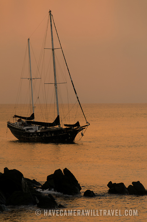 A two-mast old sailing boat is silhouetted against the setting sun while moored in calm waters of Gallows Point on St. John, in the US Virgin Islands.