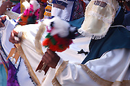 Bolivia.Tarija. San Roque. During the procession.The Chuncho marks the time of the music using a wooden instrument that arrow. That, as a veil on the face and also the bright color of the costume are legacies of the era of leprosy