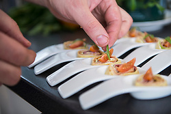 Cook preparing and decorating pancake wraps as appetizers on porcelain spoons