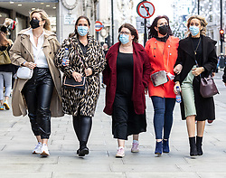 Licensed to London News Pictures. 24/10/2021. London, UK. Sunday shoppers wear masks on Oxford Street, London today as Health Secretary Sajid Javid orders the NHS to allow the over 50s to book their 3rd vaccine a month early to speed up the booster vaccination program. This week, Downing Street predicted new infections could rise to 100,000 a day this winter and urged eligible members of the public to get their booster jabs as soon as possible. Photo credit: Alex Lentati/LNP