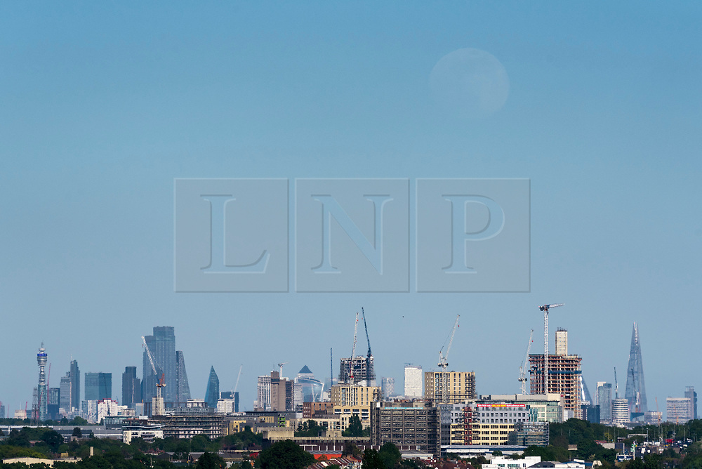 © Licensed to London News Pictures. 05/05/2020. LONDON, UK.  A 95% waxing gibbous moon rises through the haze over the capital as the UK enters its sixth week of coronavirus lockdown.  The forecast for the next few days is for sunshine and dry conditions ahead of this month's full moon on 7 May, which is known as the Flower Moon.  Photo credit: Stephen Chung/LNP