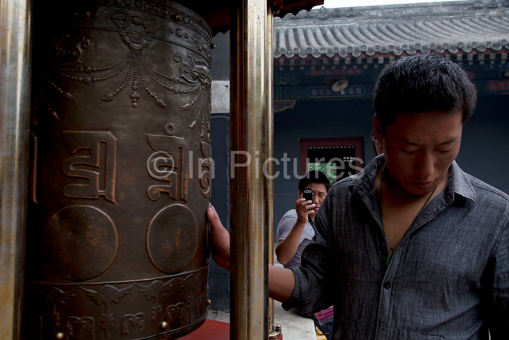 "Man turning a prayer wheel at Yonghe Temple, also known as the ""Palace of Peace and Harmony Lama Temple"", the ""Yonghe Lamasery"", or - popularly - the ""Lama Temple"" is a temple and monastery of the Geluk School of Tibetan Buddhism located in the northeastern part of Beijing, China. It is one of the largest and most important Tibetan Buddhist monasteries in the world. The building and the artworks of the temple is a combination of Han Chinese and Tibetan styles."