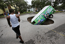 A van remains in a sinkhole on Monday, September 11, 2017, that opened up at the Astor Park apartment complex in Winter Springs, FL, USA, during Hurricane Irma's passing through central Florida Sunday night. The glass on the ground is the window that the driver punched out to extract himself after driving into the sinkhole. Photo by Joe Burbank/Orlando Sentinel/TNS/ABACAPRESS.COM