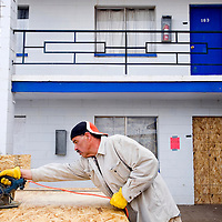 022013       Cable Hoover<br /> <br /> Maintenance worker Serafin Chavez cuts plywood to cover the windows and door of the Thunderbird Motel in Gallup Wednesday. The hotel was closed by the city following complications from a burst sewage line.